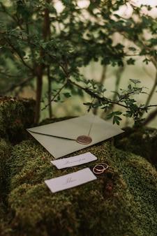 コケの上に横たわる結婚式の招待状 Premium写真