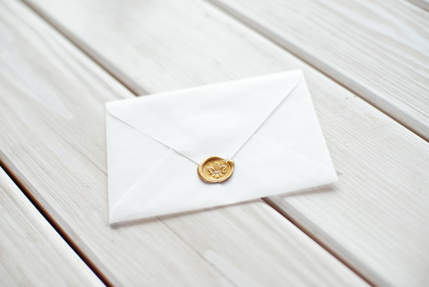Wedding invitation as a decorated letter on a white tablecloth.