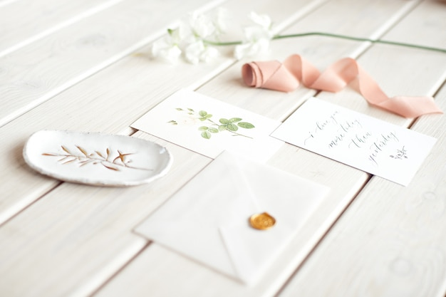 Wedding invitation birthday gift certificate for a spa or care decorated letter card on a white wooden table with a branch of white flowers.