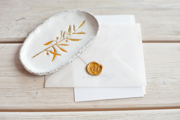 Wedding invitation birthday gift certificate for a spa or care decorated letter card on a white wooden table with a ceramic plate in rustic style.