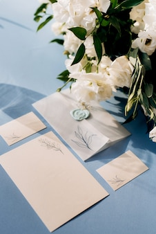 Wedding invitation in a blue envelope on a table with green sprigs