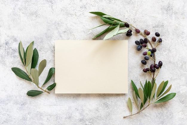 올리브 가지로 장식된 대리석 탁자 위에 놓인 결혼식 초대장. 세로 빈 종이 카드와 함께 우아한 현대 템플릿입니다. 텍스트를 위한 장소가 있는 지중해 플랫 레이 모형