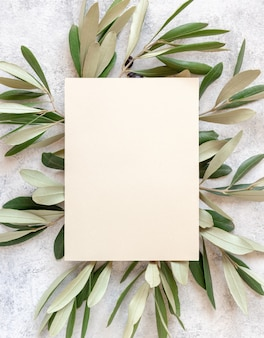 Свадебные приглашения на мраморном столе, украшенном оливковыми ветвями. элегантный современный шаблон с вертикальной пустой бумажной карточкой. средиземноморский плоский макет с местом для текста
