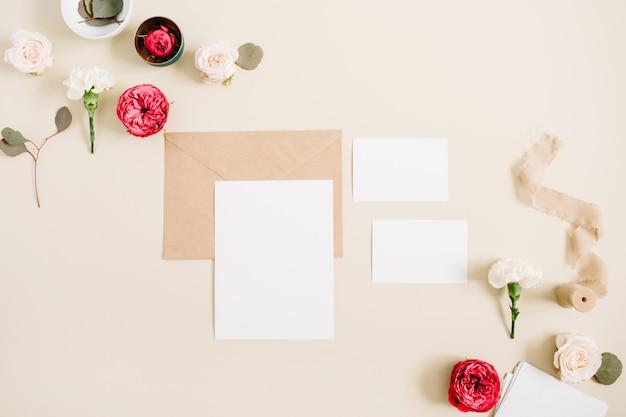 Свадебные приглашения, крафтовый конверт, бутоны розовых и красных роз и белая гвоздика на бледно-пастельно-бежевом фоне