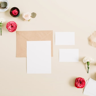 Wedding invitation cards, craft envelope, pink and red rose flower buds and white carnation. flat lay, top view