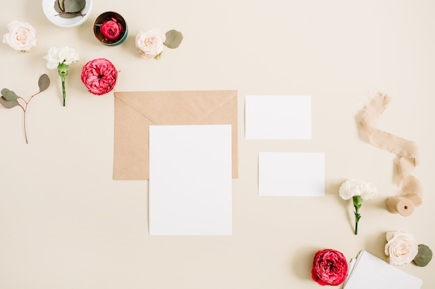 Wedding invitation cards, craft envelope, pink and red rose flower buds and white carnation on pale pastel beige
