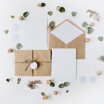 Свадебные приглашения, ремесленные конверты, розовые и красные розы и зеленые листья на белом