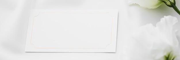 結婚式の招待状またはギフトカードとブライダルフラットレイの背景としてシルク生地に白いバラの花...