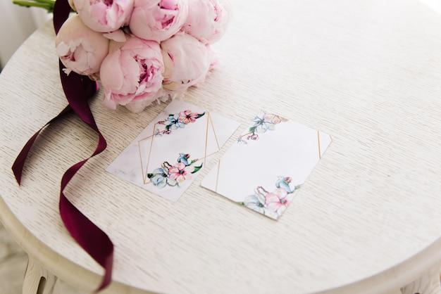 ピンクの牡丹の美しい花束の横にある結婚式の招待状