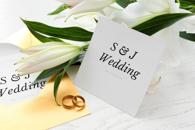 Wedding invitations, rings and flowers on table