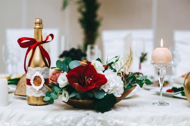 ウェディングアイテム。シャンパンとキャンドルのボトルの近くのホールのテーブルの上に立っている金のスタンドの赤い色調のフラワーアレンジメントのクローズアップ。