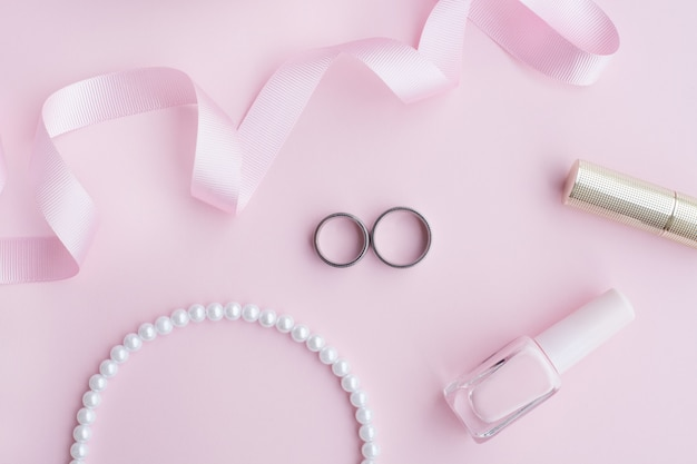 Обручальные кольца в композиции на розовом фоне