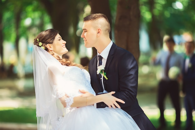 Wedding, just married couple kiss in a park, wedding concept.