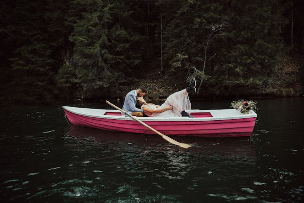 Wedding kiss on the retro boat.bride and groom sitting in pink boat floating on the lake.