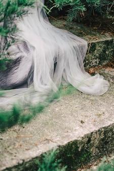 웨딩 레이스 텍스처는 돌 계단에 웨딩 드레스 가장자리를 닫습니다