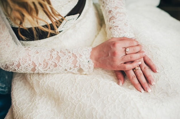 Wedding manicure close up. hands on dress. beautiful, stylish dress with french lace. two gold rings arms. bride sitting in a waiting groom husband.