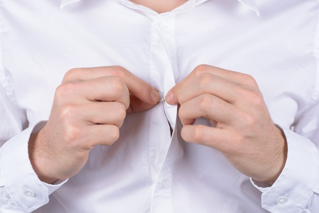 Wedding marriage preparation concept. cropped close up photo of graceful serious gentleman touching small button with fingers isolated grey background
