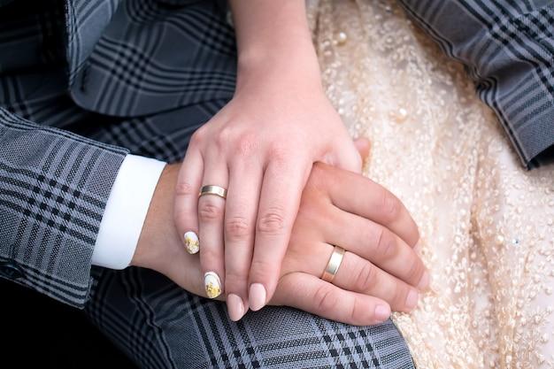 手を繋いでいる幸せなカップルの結婚式、新郎新婦、結婚指輪