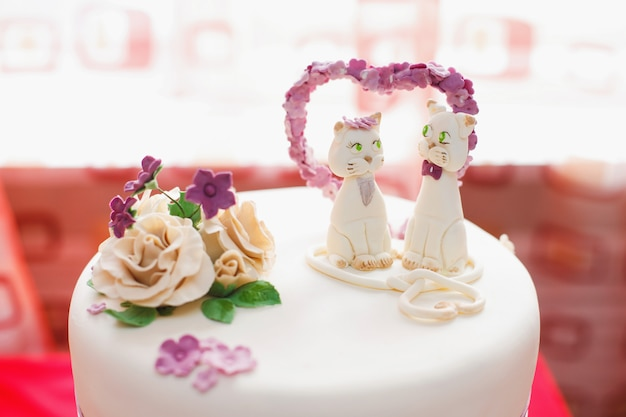 Wedding mastic cake decorated with flowers and cat figures, closeup