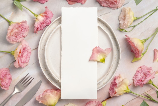 Wedding menu laying on a ceramic plate on a marble table decorated with flowers and ribbons