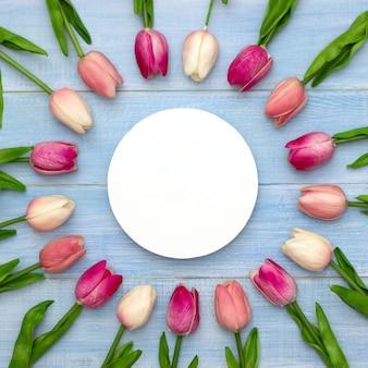 丸いホワイトペーパーと青いテーブルトップビューでピンクのチューリップの花の結婚式のモックアップ。美しい花柄。平干しスタイル。