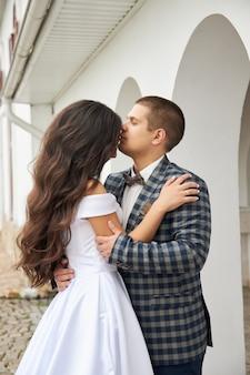 Свадьба влюбленной пары на природе у маяка. объятия и поцелуи жениха и невесты
