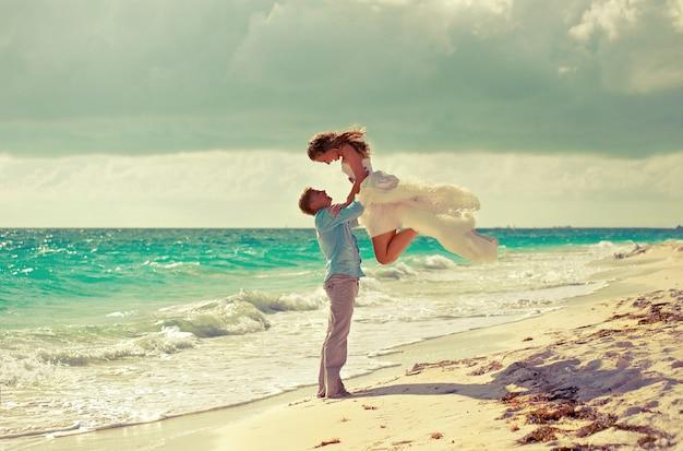 熱帯のビーチでの結婚式上から来た愛若い美しいカップルが熱帯の島のビーチで結婚した愛する人の手に若い花嫁愛と幸福の象徴