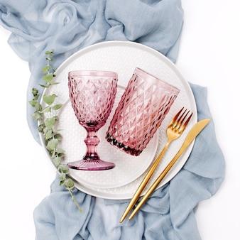 結婚式やお祝いのテーブルセッティング。白い背景に灰色の装飾的な織物とプレート、ワイングラス、カトラリー。美しいアレンジ。