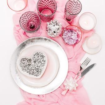 結婚式やお祝いのテーブルセッティング。プレート、ワイングラス、キャンドル、白い背景に装飾的なテキスタイルのカトラリー。ピンク色の美しいアレンジメント