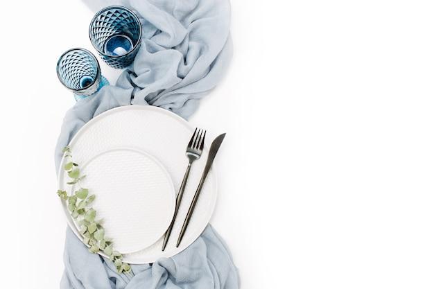 結婚式やお祝いのテーブルセッティング。プレート、ワイングラス、キャンドル、カトラリー、白い背景に灰色の装飾的なテキスタイル。美しいアレンジ。