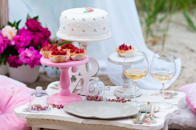 Wedding or party candy bar, decorated dessert table in pink color with cakes