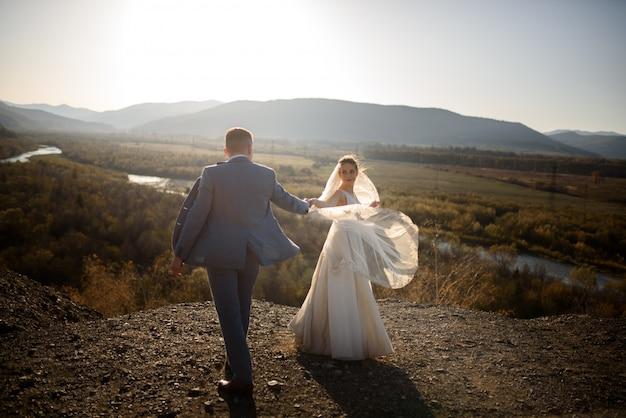 山の新郎新婦の結婚式のフォトセッション。夕暮れ時の写真撮影。