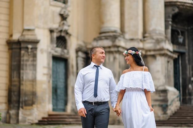 古い教会の背景に結婚式の写真セッション。新郎新婦が一緒に歩いています。男性が女性の手を握る素朴なまたは自由奔放に生きるスタイルの結婚式の写真