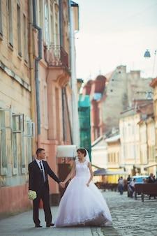 Свадебная фотосъемка. невеста и жених гуляя в город. семейная пара обнимает и глядя друг на друга. держа букет. открытый, полное тело