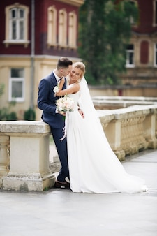 Wedding photo shooting. bride and bridegroom walking in the city. married couple embracing and looking at each other. holding bouquet. outdoor, full body