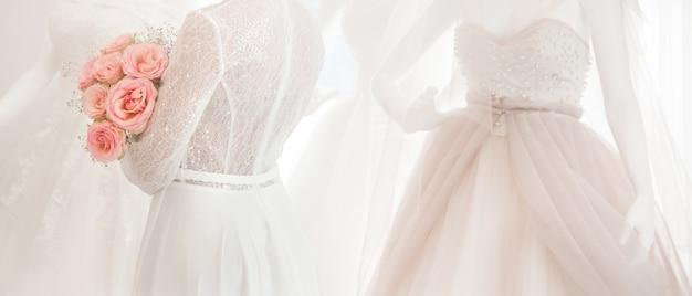 白いドレスと明るい背景の上のピンクのバラの花束との結婚式の写真