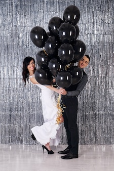Свадебная фотография. молодая пара с черными шарами на блестящем фоне