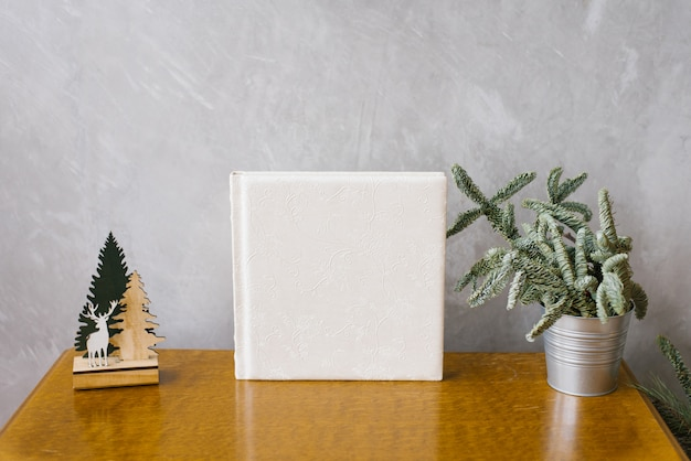 Wedding photobook in white leather cover surrounded by a christmas tree in a metal bucket