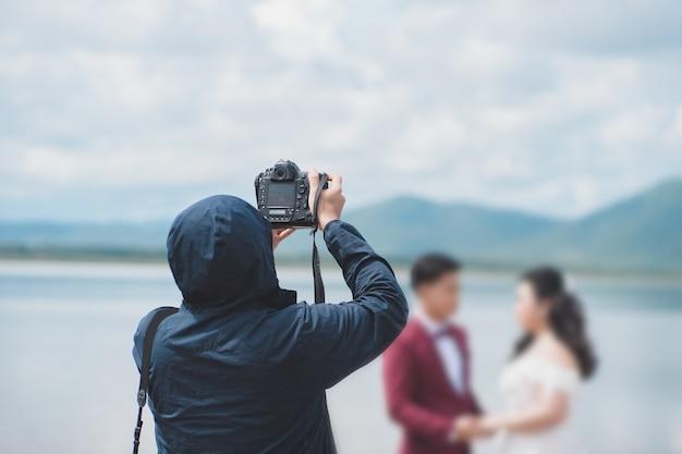 自然の中で新郎新婦の結婚式の写真家の写真。