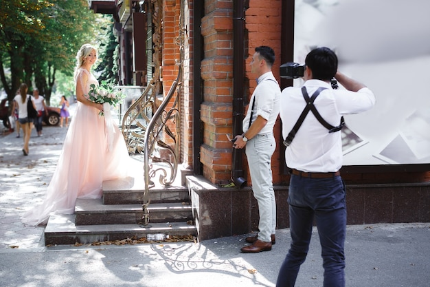 Wedding photographer takes pictures of bride and groom in city. wedding couple on photo shoot. photographer in action