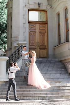 Свадебный фотограф фотографирует жениха и невесту в городе. свадебная пара на фотосессии. фотограф в действии