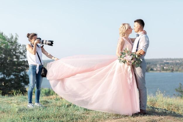 Свадебный фотограф фотографирует жениха и невесту на природе. свадебная пара на фотосессии. фотограф в действии