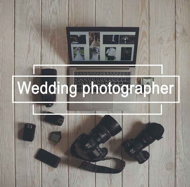 Wedding photographer work tools flat lay. top view on photo cameras with equipment, smartphone, bundle of money and laptop with wedding photos