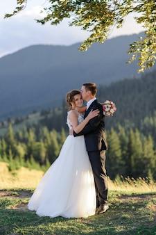 산에서 웨딩 사진. 신랑은 이마에 신부에게 키스합니다. 신부는 프레임을 들여다 본다.