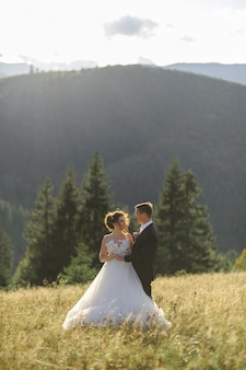 Wedding photography in the mountains. the groom hugs the bride. newlyweds look into each other's eyes.
