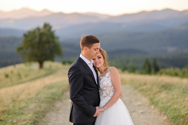Wedding photography in the mountains. newlyweds are hugging. close-up. the bride looks into the frame.