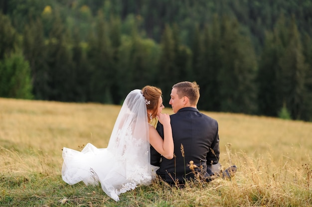 Wedding photography in the mountains. newlyweds sit with their backs on the grass and look at each other.