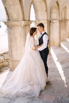 モンテネグロの結婚式の写真撮影ペラスト結婚式のカップルが古い石の柱に寄り添う