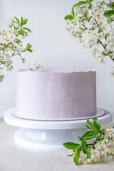 Wedding pink cake cake on a stand among branches of cherry blossoms.