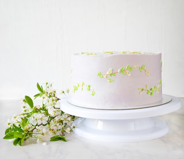 Wedding pink cake on a stand with branches of cherry blossoms. delicate decor on cake.
